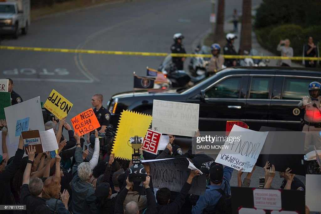 The presidential motorcade passes activists demonstrating near a Hillary Clinton presidential campaign fundraiser featuring US President Barack Obama to call for a halt to the Dakota Access Pipeline project on October 24, 2016 in Beverly Hills, California. / AFP / DAVID