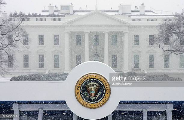The presidential seal affixed to the top of the Inaugural viewing stand is seen in front of the White House during snow flurries January 19 2005 in...