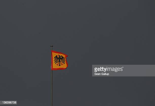The Presidential standard lit by the sun flies over Schloss Bellevue presidential palace as dark clouds pass behind on January 4 2012 in Berlin...
