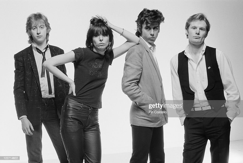 The Pretenders (guitarist James Honeyman-Scott (1956-1982), singer and guitarist Chrissie Hynde, bassist Pete Farndon (1952-1983), and drummer Martin Chambers), British rock band, pose for a group studio portrait, against a white background, United Kingdom, in January 1979. Hynde leans against Farndon with her elbow on his shoulder.