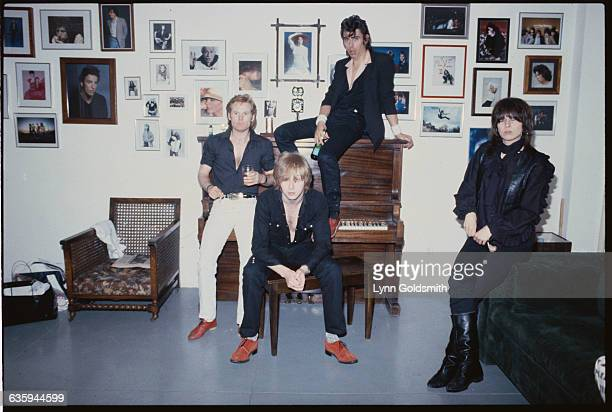 The Pretenders in a photographer's studio. From left, they are Martin Chambers, James Honeyman-Scott, Peter Farndon sitting on top of the piano, and...