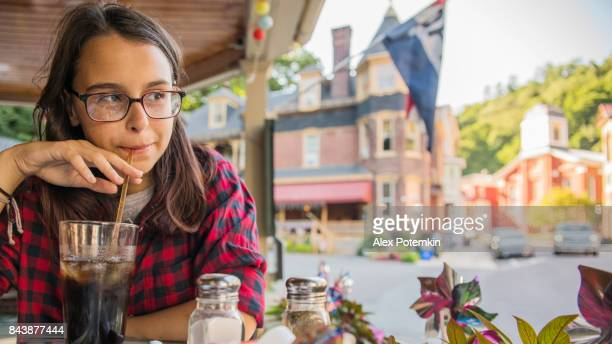 the pretty 16 years old teenager girl eating in the street cafee in jim thorpe, poconos region, pennsylvania - jim thorpe pennsylvania stock photos and pictures