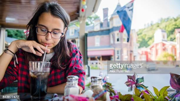 la chica de adolescente de 16 años bastante comiendo en la calle cafee en jim thorpe, región de poconos, pennsylvania - linda pop fotografías e imágenes de stock