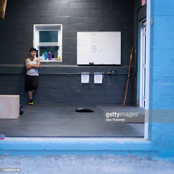 the pretty cheerful athletic young latino woman with the tattoo in the gym - alex potemkin or krakozawr latino fitness stock photos and pictures