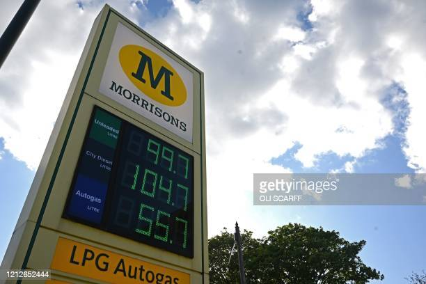 The price in GBP of unleaded petrol at 997p and diesel fuel at £1047 is displayed on an electronic board at a Morrisons petrol station in Manchester...