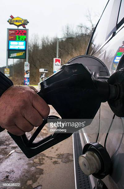 The price of regular unleaded and diesel fuels are displayed on a sign as a customer fuel a vehicle at a Sunoco Inc gas station in Rockbridge Ohio US...