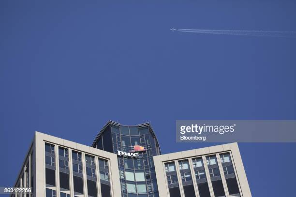 The PricewaterhouseCoopers LLP logo sits on 51-storey skyscraper Tower 185 as an aircraft flies above in Frankfurt, Germany, on Wednesday, Oct. 18....