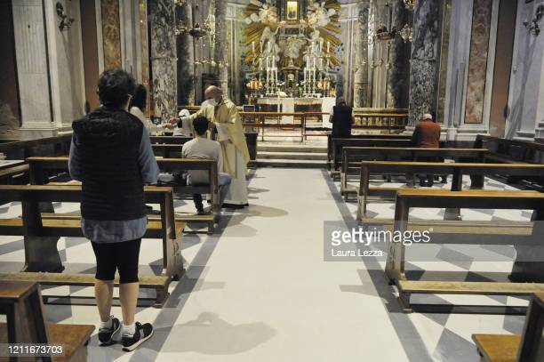 The priest gives communion to the faithful during the Sunday mass maintaining the social distance to guarantee health safety standards at Santuario...