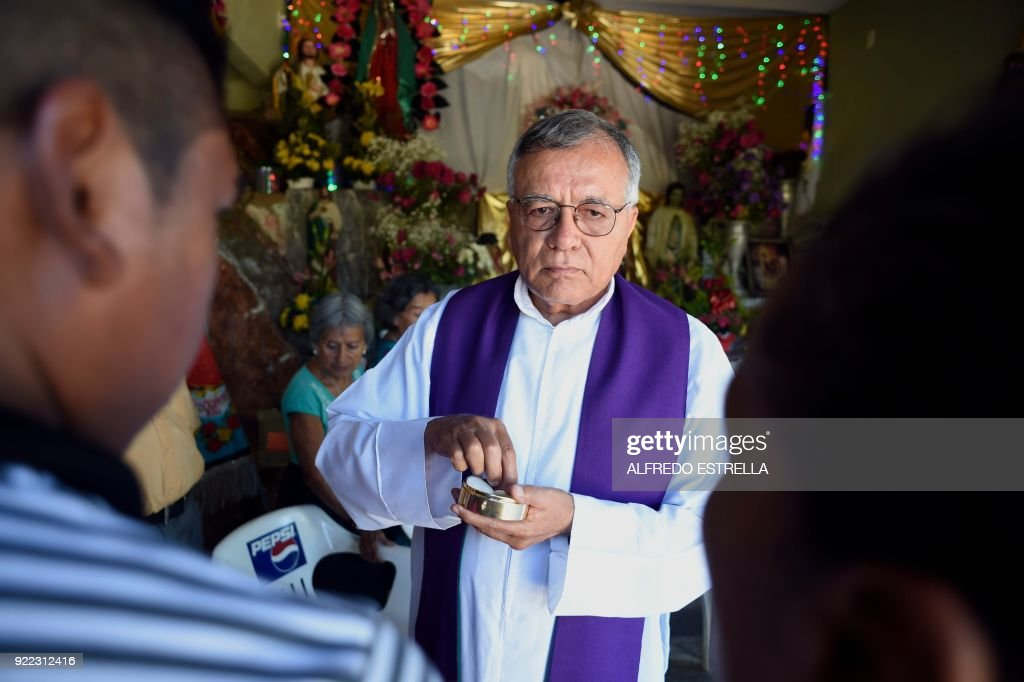 The priest Jesus Mendoza give the Eucharistia during a mass at Kilometro 30 community near the Acapulco resort in Guerrero State, Mexico, on February 14, 2018. Violence in the state of Guerrero claimed the lives of two priests on February 5, 2018. / AFP PHOTO / Alfredo ESTRELLA / TO