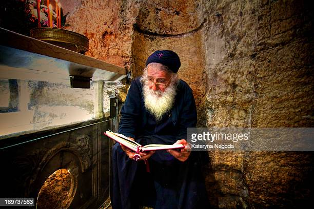 The priest reads the bible by the sarcophagus in Mary's Tomb. Church of the Sepulchre of Saint Mary, also Tomb of the Virgin Mary, refers to a...