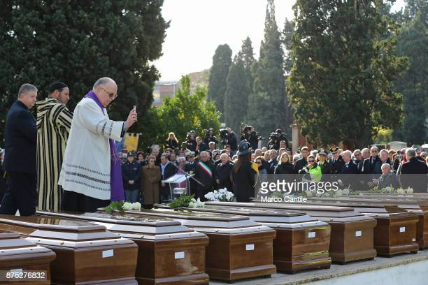 The priest together with a Muslim representative blesses the coffins during the funeral of the 28 migrant women who died in a shipwreck as they...