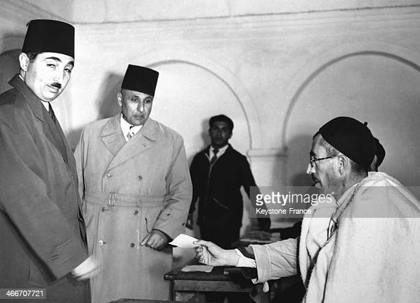 The Prime Minister Mahmud Bey Muntasser receives his voting card at the Hamura Mosque on the outskirts of Tripoli which was turned into a polling...