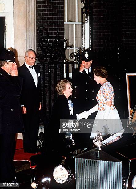 The Prime Minister Margaret Thatcher Curseying To The Queen At 10 Downing Street. Her Husband Dennis Thatcher Is Standing Behind.