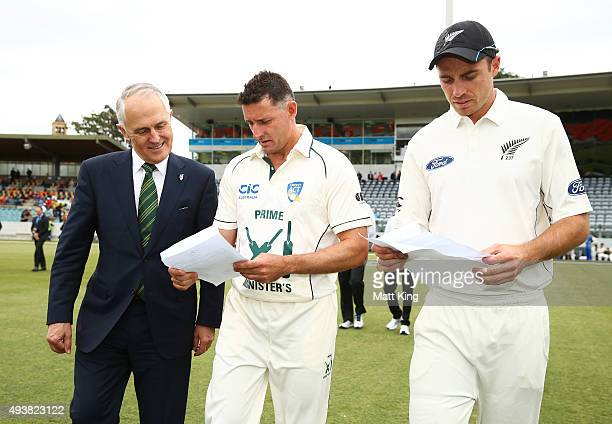 The Prime Minister of Australia Malcolm Turnbull checks the final team sheets with the Prime Minister's XI captain Michael Hussey and New Zealand...