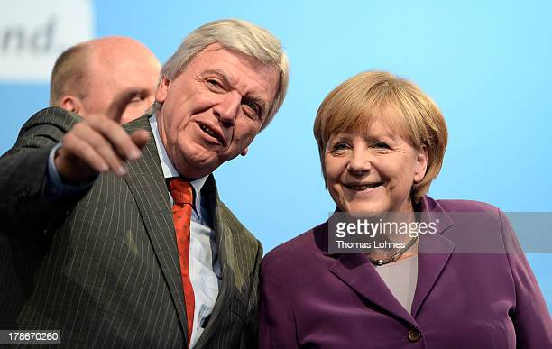 The prime minister of Hesse Volker Bouffier shows the German Chancellor and Chairwoman of the German Christian Democrats Angela Merkel the protestors...