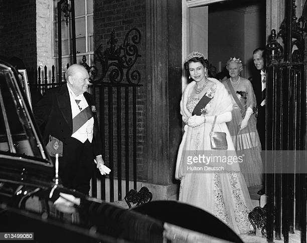 The Prime Minister Winston Churchill holds open the door of the Royal car for the Queen and the Duke of Edinburgh as they leave 10 Downing Street...