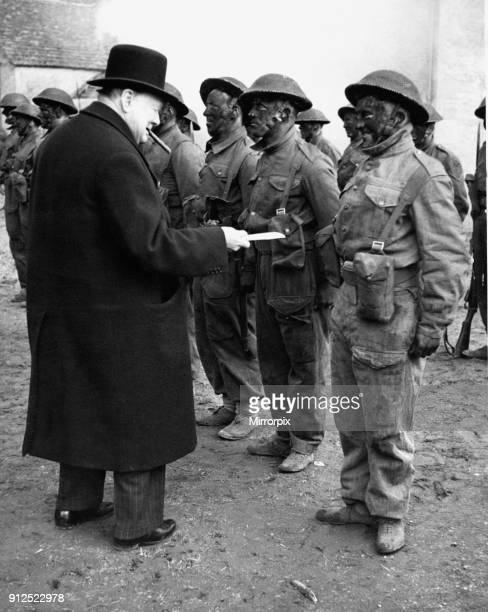 The Prime Minister Winston Churchill watched an exercise by troops on commando lines He is examining the knife used by one of the men with blackened...
