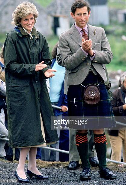 The Prince And Priness Of Wales Applauding Whilst Visiting Barra In The Western Isles. She Is Wearing A Barbour Style Waterproof Coat In The Rain.