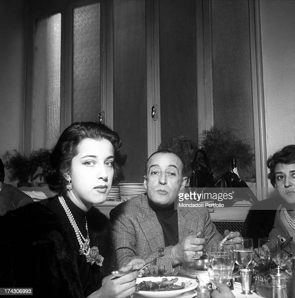 The prince from Naples Antonio de Curtis, known as Totò, is seated and having dinner in a restaurant with his daughter Liliana and his partner, the...