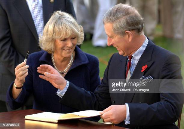 The Prince of Wales and the Duchess of Cornwall giggle as they sign the visitors book at the Seed School on the outskirts of Washington DC Wednesday...