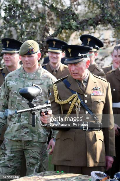 The Prince of Wales fires a paintball gun as he meets personnel from 1st Battalion The Welsh Guards during a visit to their barracks in Hounslow...