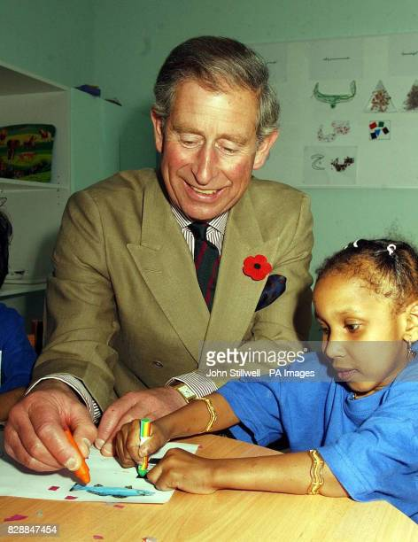 The Prince of Wales helps a child with her colouring in at the Association of early intervention for children with special needs in Muscat This...