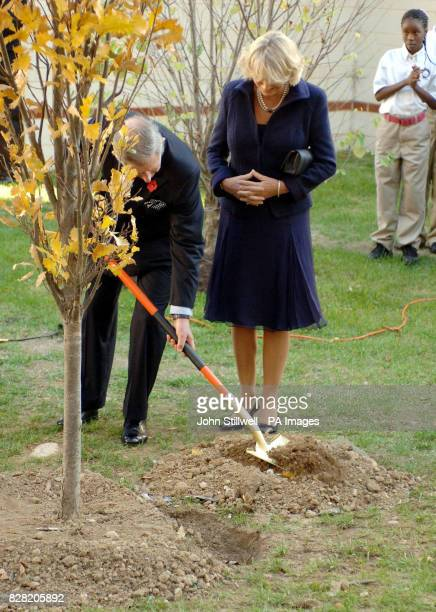 The Prince of Wales helps to plant a tree watched by his wife the Duchess of Cornwall after they toured the Seed School on the outskirts of...