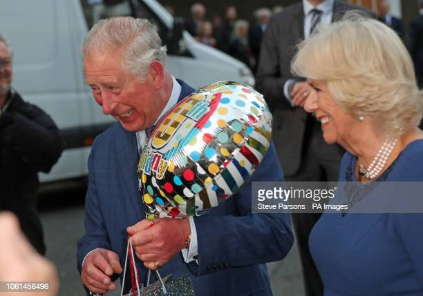 The Prince of Wales holds a birthday gift as he and the Duchess of Cornwall arrive for a tea party at Spencer House in London to celebrate 70...