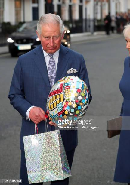 The Prince of Wales holds a birthday gift as he arrives for a tea party at Spencer House in London to celebrate 70 inspirational people marking their...