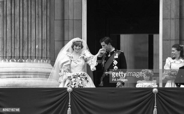 The Prince of Wales kisses the hand of his new bride the Princess of Wales on the balcony of Buckingham Palace To the right are two of the...