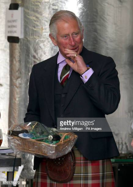The Prince of Wales known as the Duke of Rothesay while in Scotland is given a gift during a visit to the John O'Groats Brewery in John O'Groats...