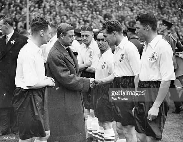 The Prince of Wales, later King Edward VIII, shakes hands with the players of Sheffield Wednesday at the FA Cup Final at Wembley Stadium. The team...