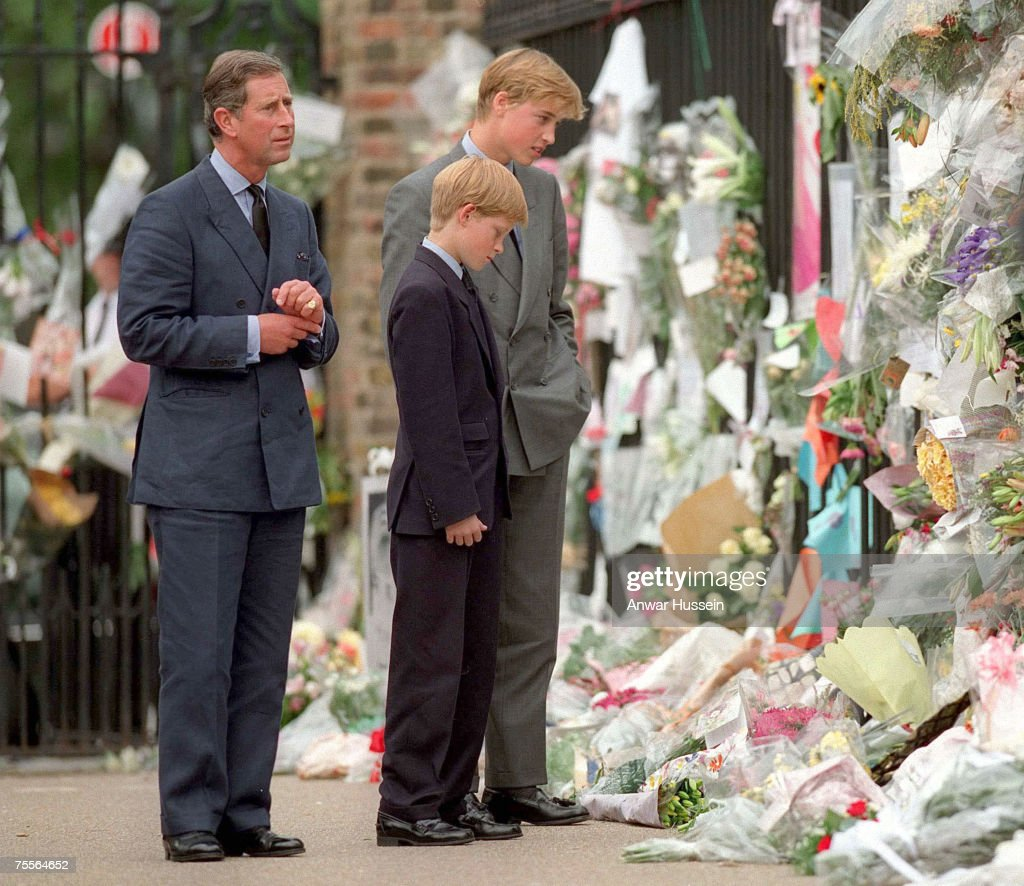 The Prince of Wales, Prince William and Prince Harry look at the floral tributes to Diana, Princess of Wales, at Kensington Palace on September 5th, 1997.
