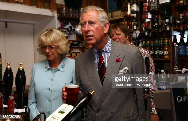 The Prince of Wales pulls a pint of Cambrian Heart beer in the bar of the Neuadd Arms Hotel Llanwrtyd Wells accompanied by the Duchess of Cornwall