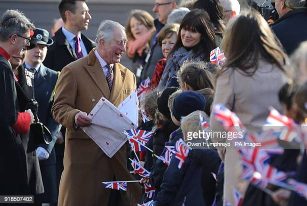The Prince of Wales receives a card for Prince Harry and Meghan Markle from pupils at the Chorister School as he arrives for a visit to the Open...