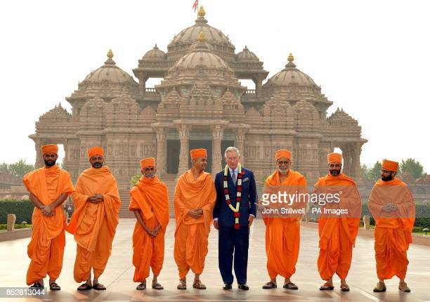 The Prince of Wales stands with priests in the grounds of the Akshardham Temple in Delhi the capital of India on the third day of their eleven day...