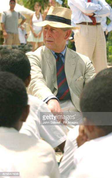 The Prince of Wales talks to a group of school children from the Malolo District School having a lesson at the edge of the Pacific Ocean