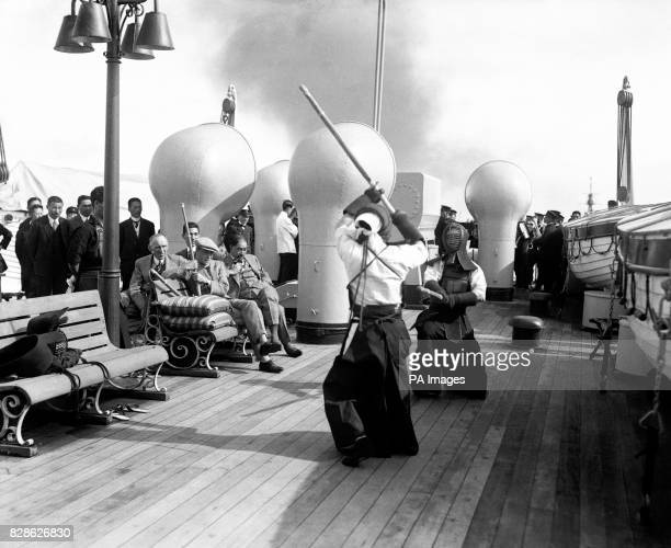 The Prince of Wales watching two members of his Japanese staff giving an exhibition of Kendo on the deck of the Japanese Railway ferry 'Keifuku Maru'