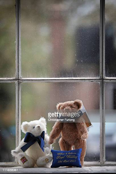 The Prince William and Catherine Middleton limited edition royal wedding teddy bears sit on the window sill at the Merrythought teddy bear factory on...