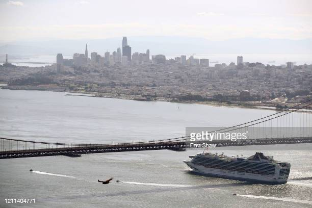 The Princess Cruises Grand Princess cruise ship heads under the Golden Gate Bridge to a port in Oakland, CA on March 09, 2020 as seen from the Marin...