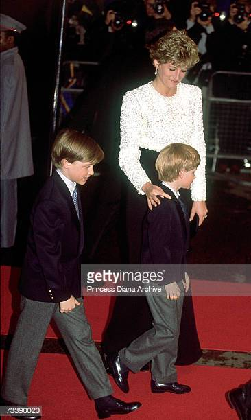 The Princess of Wales and her children Princes William and Harry arriving for the premiere of 'Hook' April 1992 Princess Diana wears a gown by...