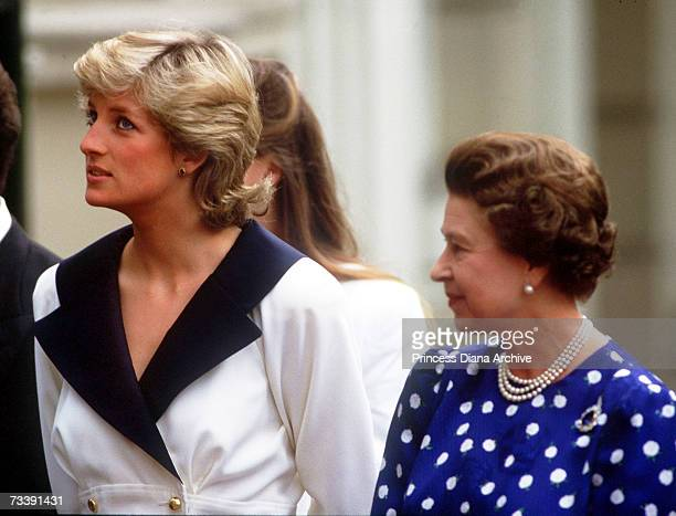 The Princess of Wales and the Queen at Clarence House to celebrate the Queen Mother's 87th birthday August 1987 Diana is wearing a white dress with a...
