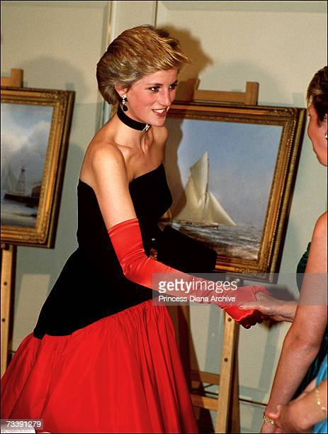 The Princess of Wales attending an America's Cup ball at the Grosvenor House Hotel September 1986 She is wearing a red and black evening gown by...