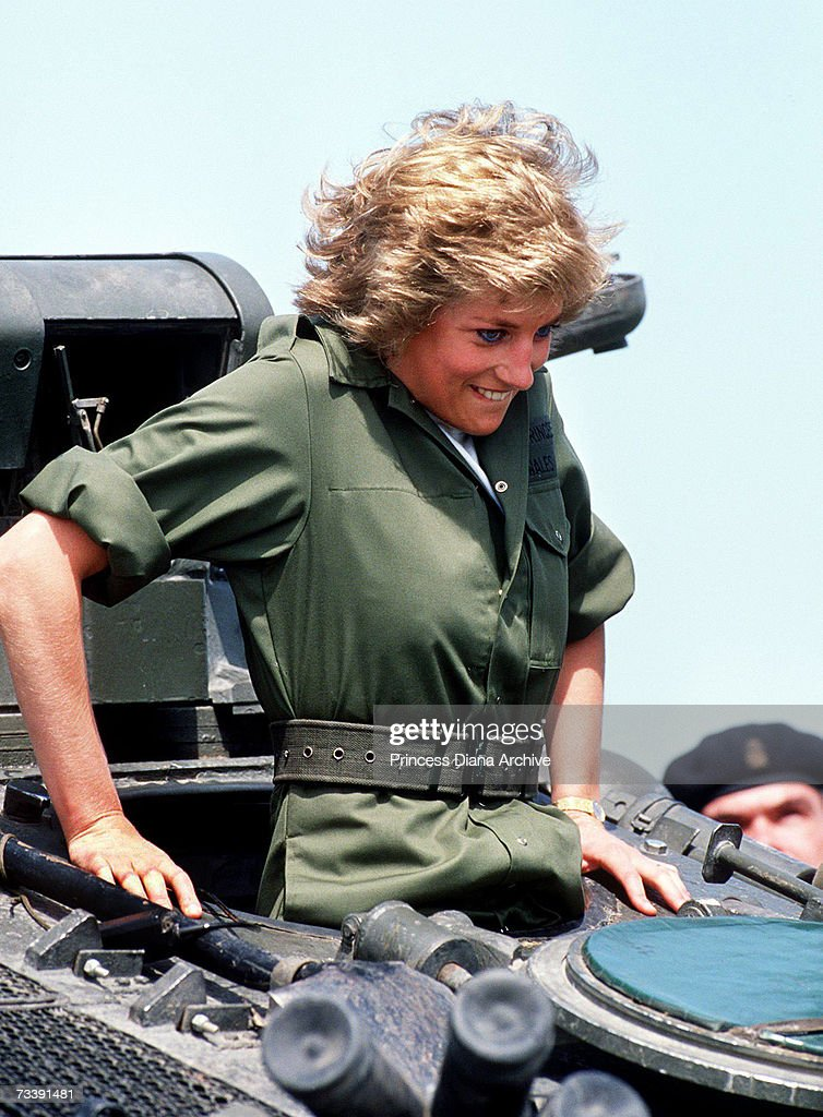 The Princess of Wales climbing into a tank during a visit to the Royal Hampshire regiment at Tidworth, June 1988. The Princess wore a boiler suit to join in with exercises.
