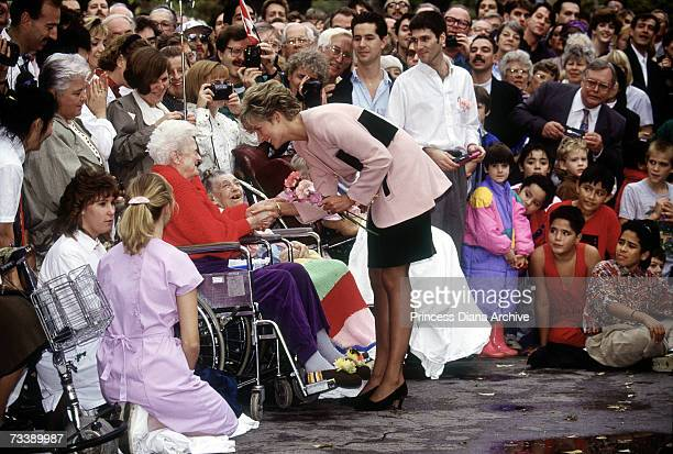 The Princess of Wales greets an old lady in a wheelchair during a visit to a hospice in Toronto October 1991