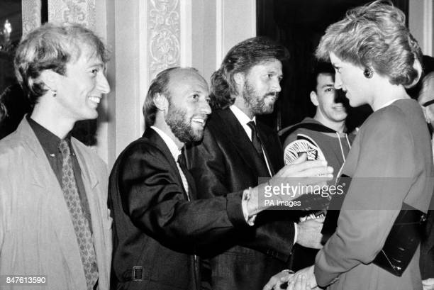 The Princess of Wales meeting the 'Bee Gees' pop group left to right Robin Maurice and Barry Gibb at London's Cafe Royale when she launched Capital...