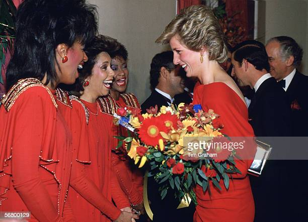 The Princess of Wales meeting the pop group The 3Degrees at the Birthright Ball wearing a red dress designed by fashion designer Bruce Oldfield