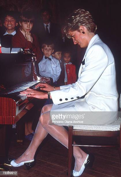 The Princess of Wales plays the piano to patients at the children's hospital in Prague May 1991