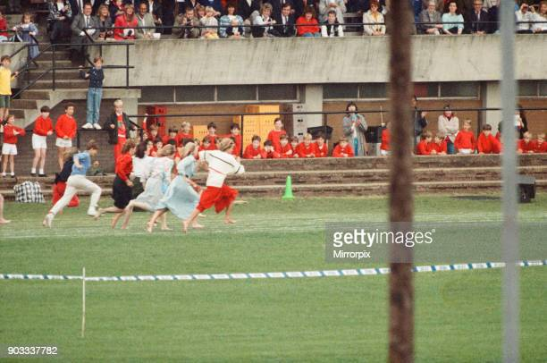 The Princess of Wales Princess Diana runs in her sons William and Harry's School Sports Day She is wearing the white top and long red skirt The...