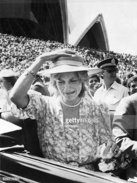 The Princess of Wales pulls a funny face as a bouquet of flowers hits her on the head when thrown from the crowd into the car. Sydney Opera House,...